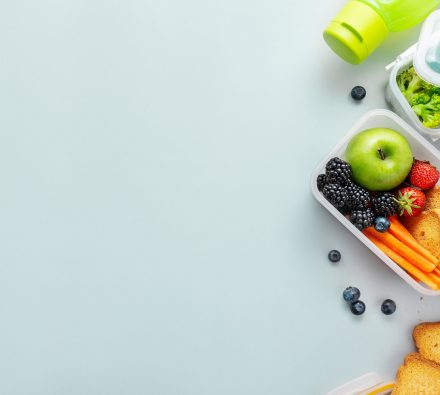 Healthy lunch to go. Fruits and vegetables packed in lunch box. Healthy eating concept. View from above with copy space.